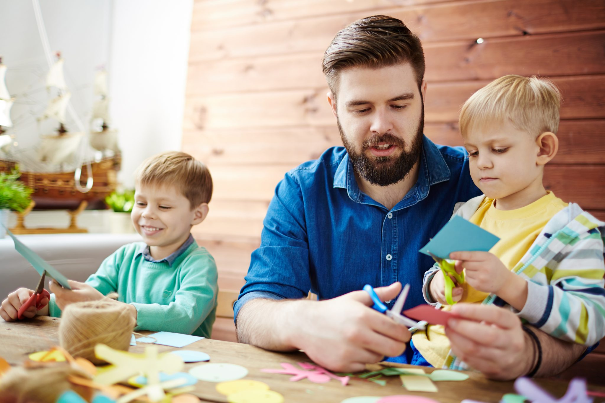 father and sons doing crafts together