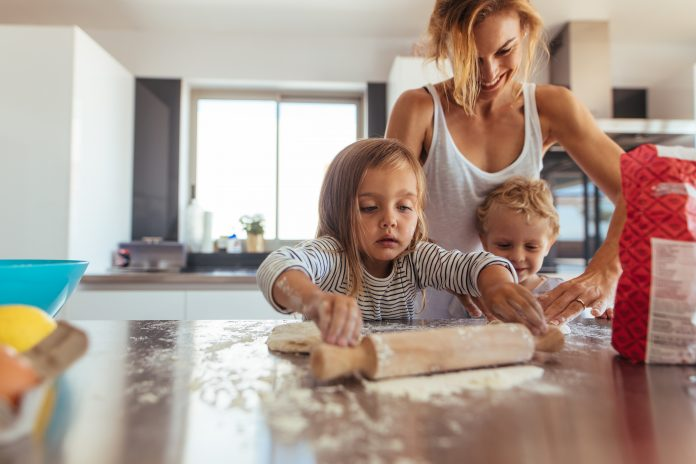 mother and two children baking in kitchen