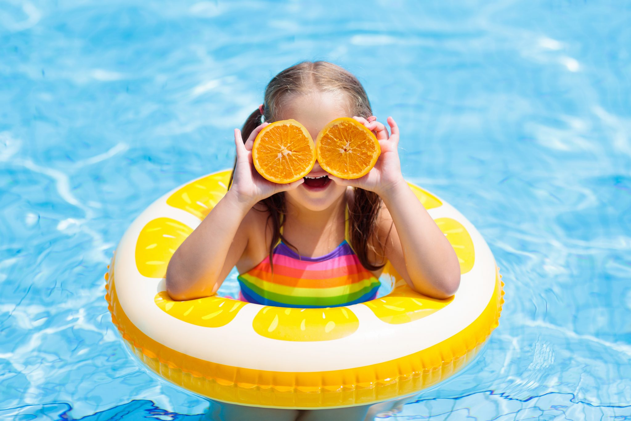Little girl in swimming pool with inflatable toy ring eating orange.