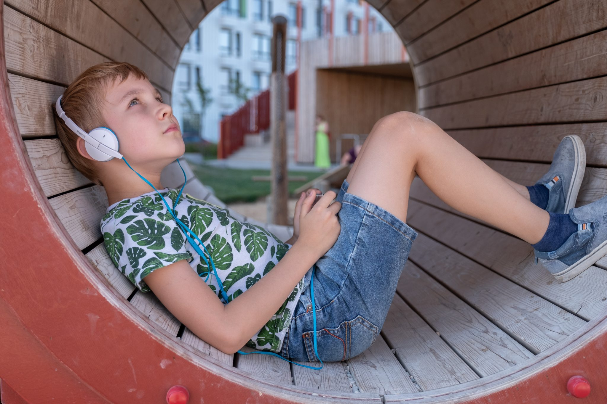 Smiling boy with smartphone and headphones listening to music or playing game outdoor
