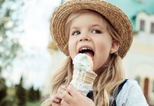 portrait of little girl in straw hat eating ice cream