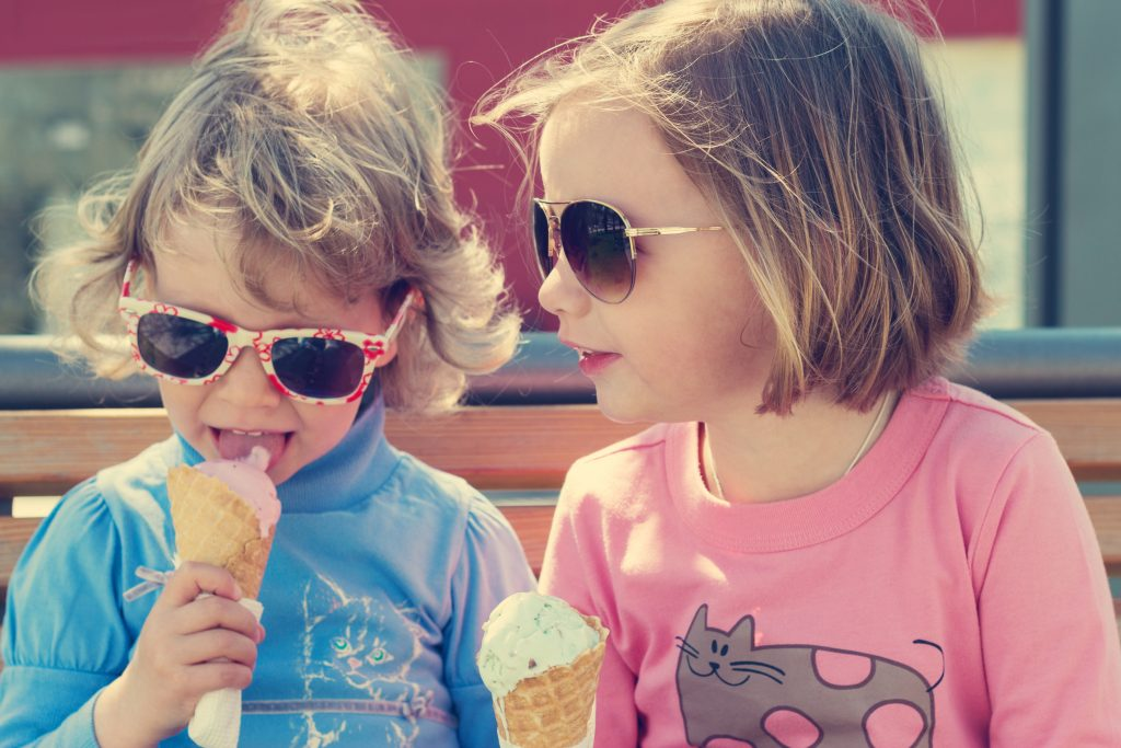 Two little girls (sisters) eating ice cream.