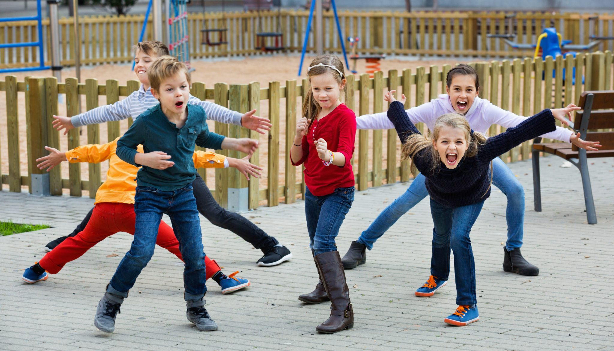 Acting game with cheerful children making performance outdoor in autumn