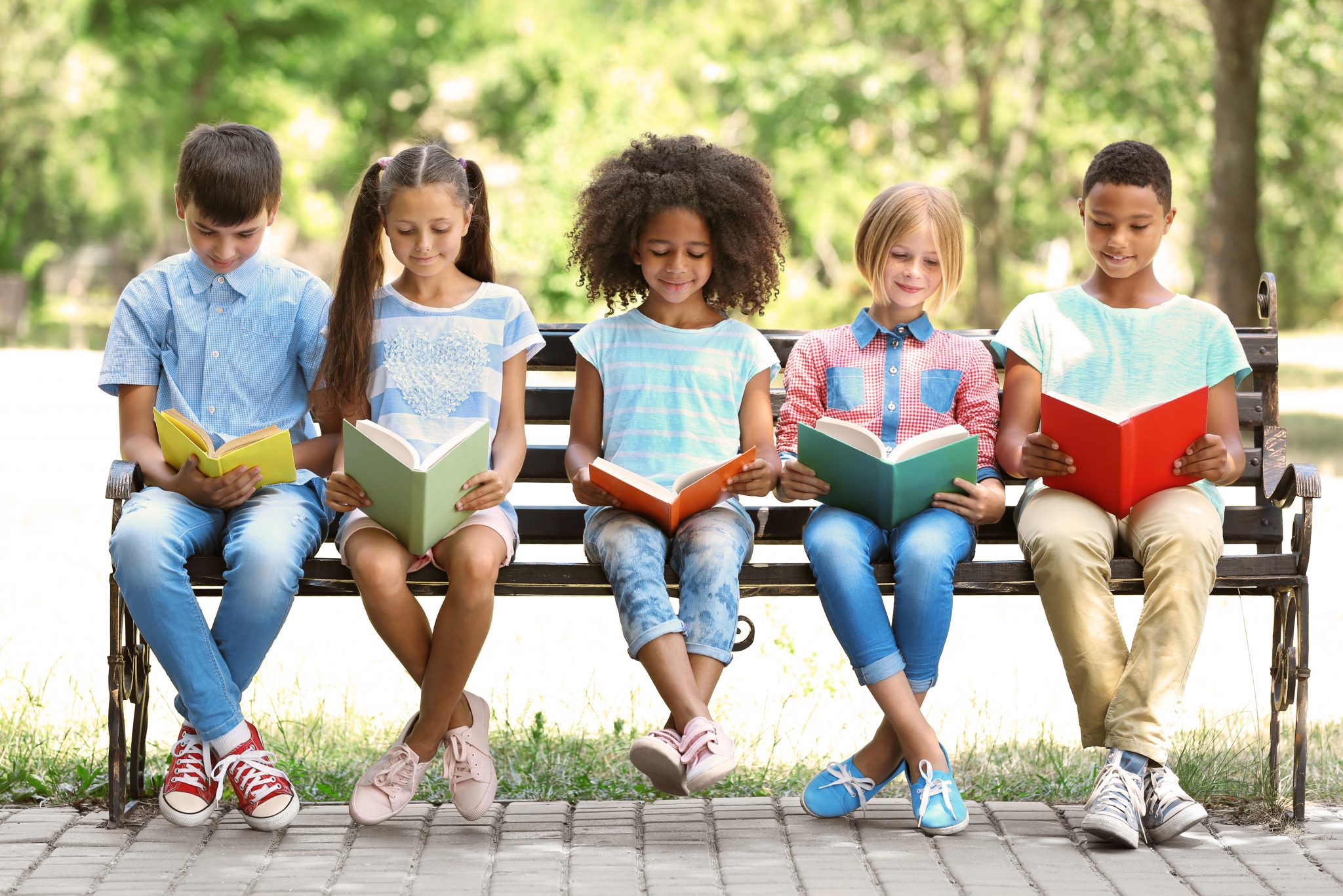 Cute kids reading books on bench