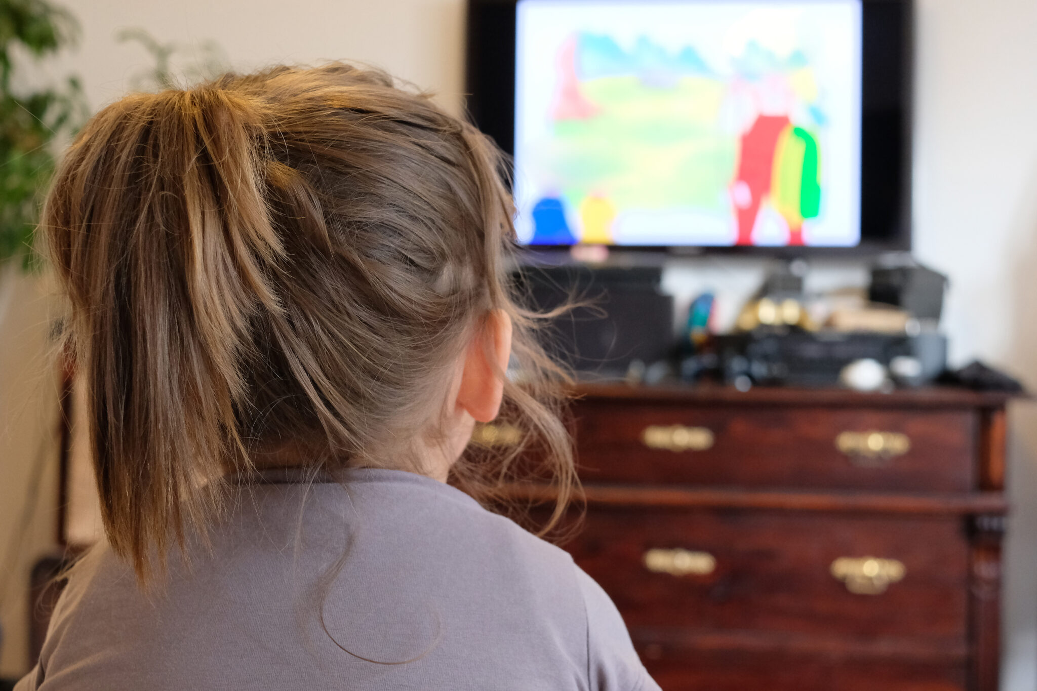 Small girl is watching a comic on TV