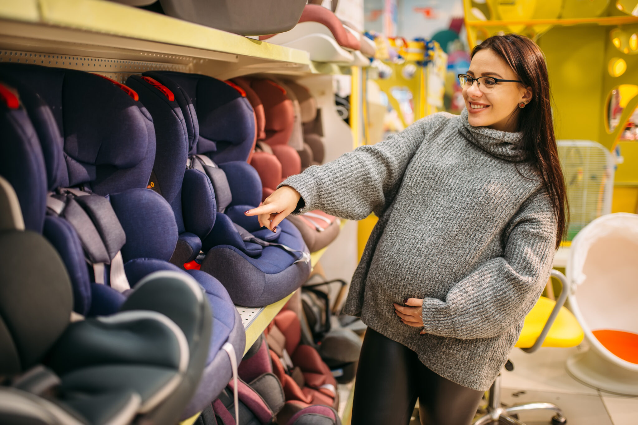 Pregnant woman choosing child car seat in store. Goods for safe children transportation