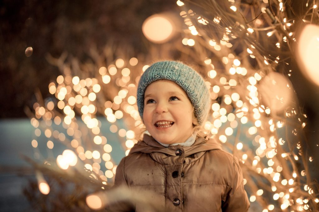 portrait of happy girl in winter evenings on background of Christmas lights, outdoor