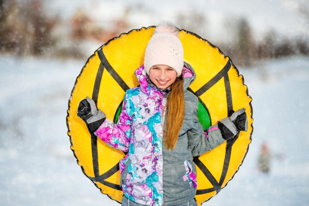 Positive active girl holding snow tubing behind her outdoors