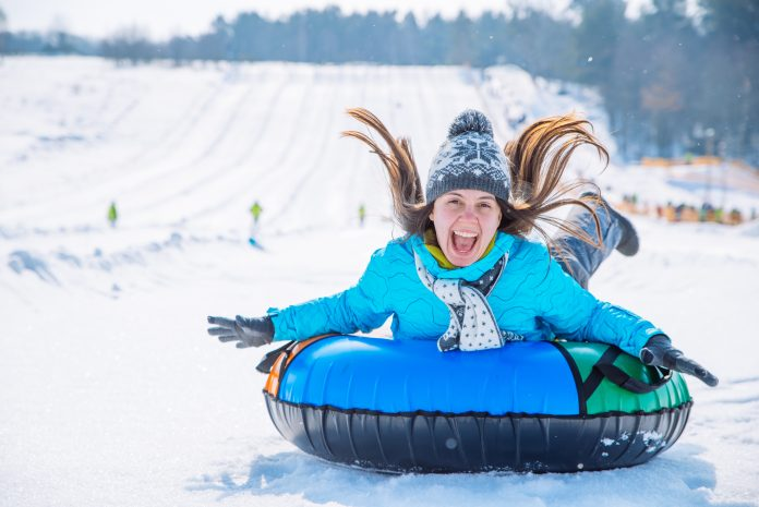 young smiling girl ride sleigh snow tubing hill winter activity concept