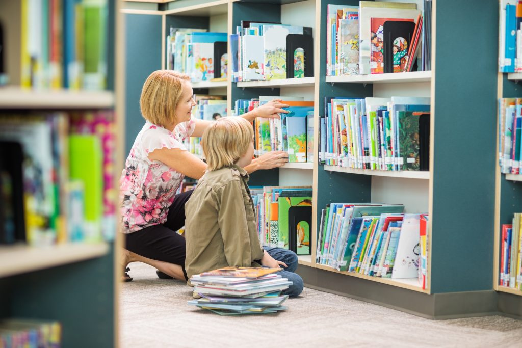 Mature teacher assisting boy in selecting books from bookshelf in library