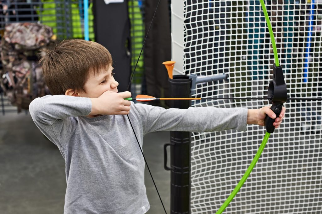 Little boy shoots a bow in a children's shooting range