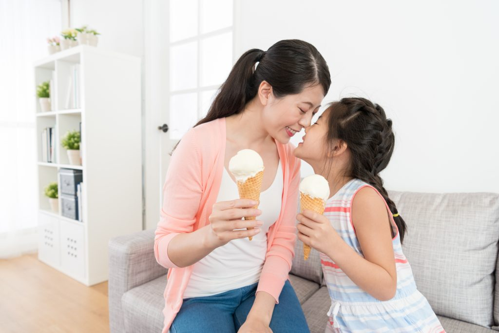 smiling pretty mom with her cute daughter sitting on living room sofa couch and eating ice cream enjoying happy moments together.