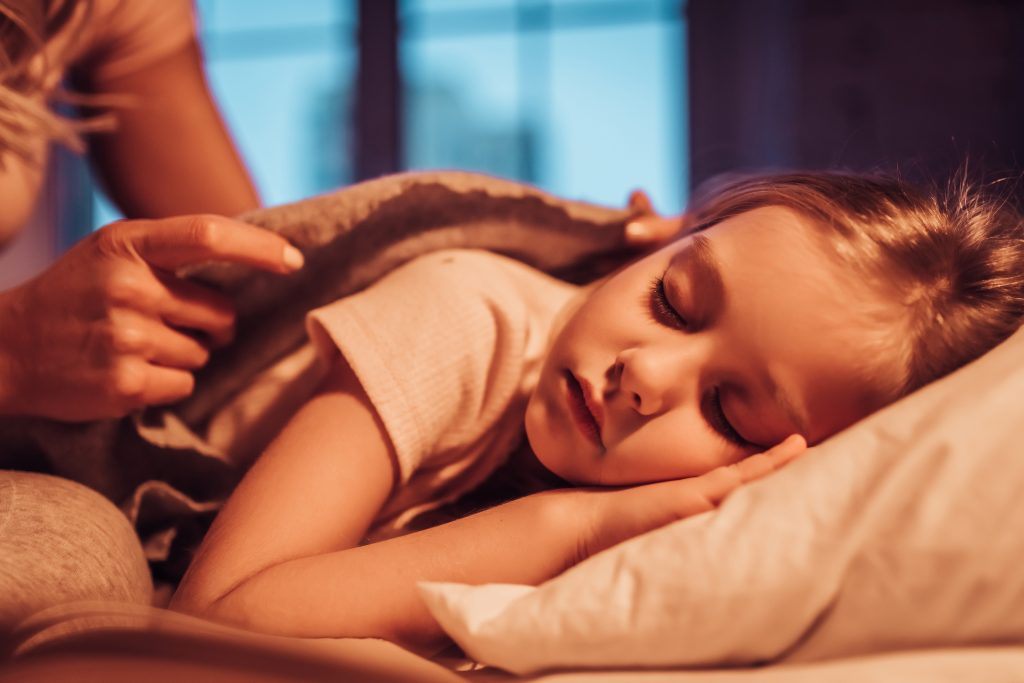 Good night, princess! Attractive young woman with little cute girl are spending time together at home. Mom is putting daughter to bed