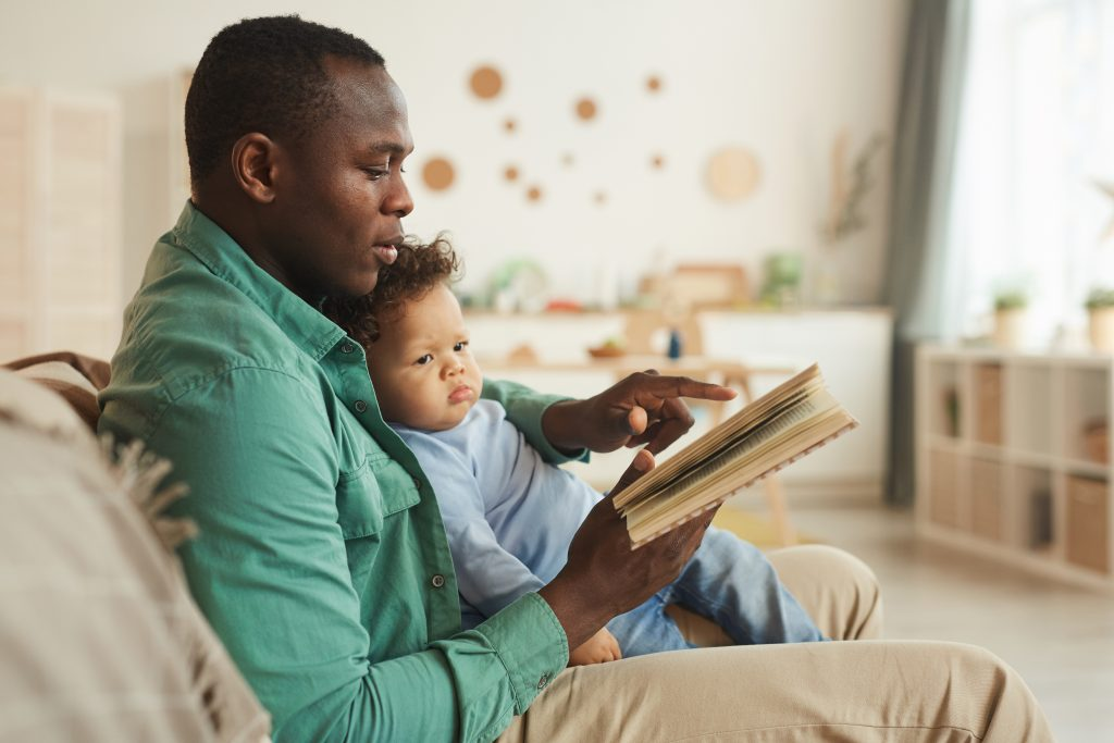 Side view portrait of caring African-American dad reading book to cute baby son at home, copy space