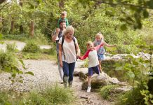 Family Hiking Along Path By River