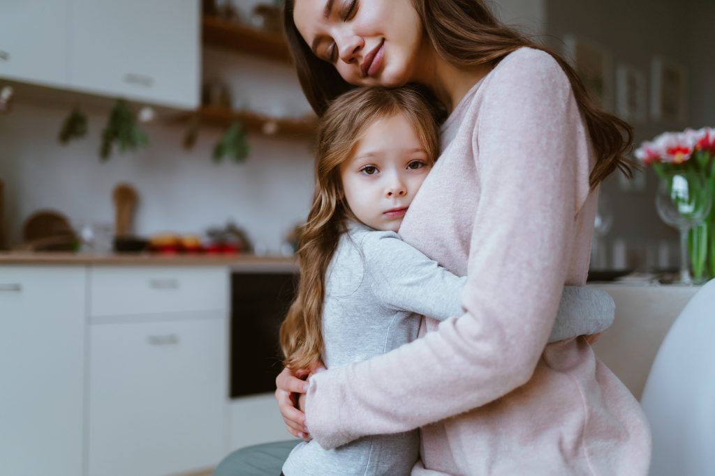 family scene daughter hugs mom with an expression of anxiety or fear mom has an expression of tenderness on her face