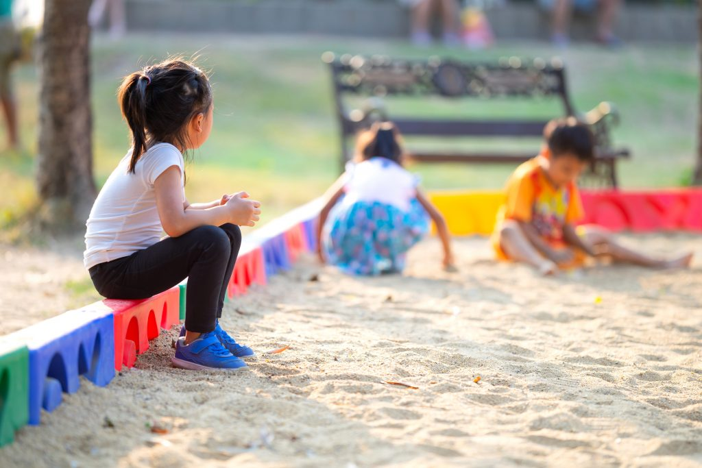 Little child girl sitting lonely watching friends play at the playground.The feeling was overlooked by other people.