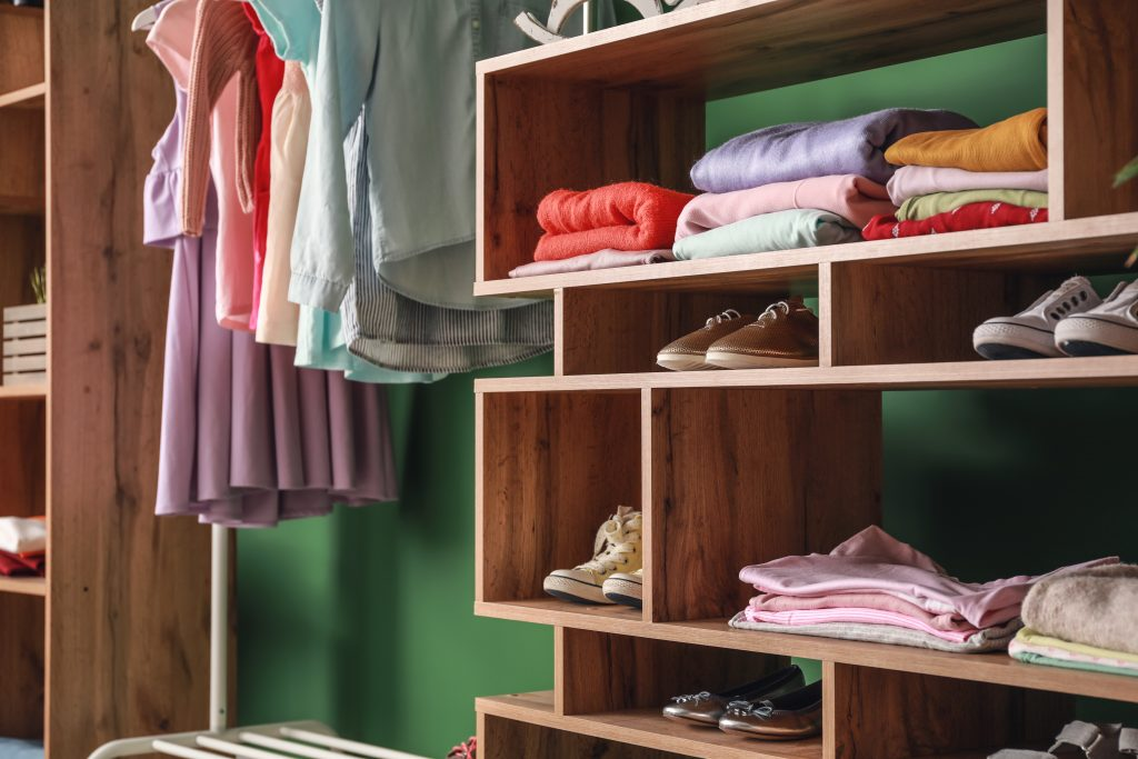 Wooden rack with children's clothes in dressing room