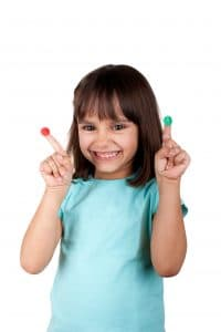 Smiling little girl with round stickers on fingers, one red and one green. Good or bad? Isolated.