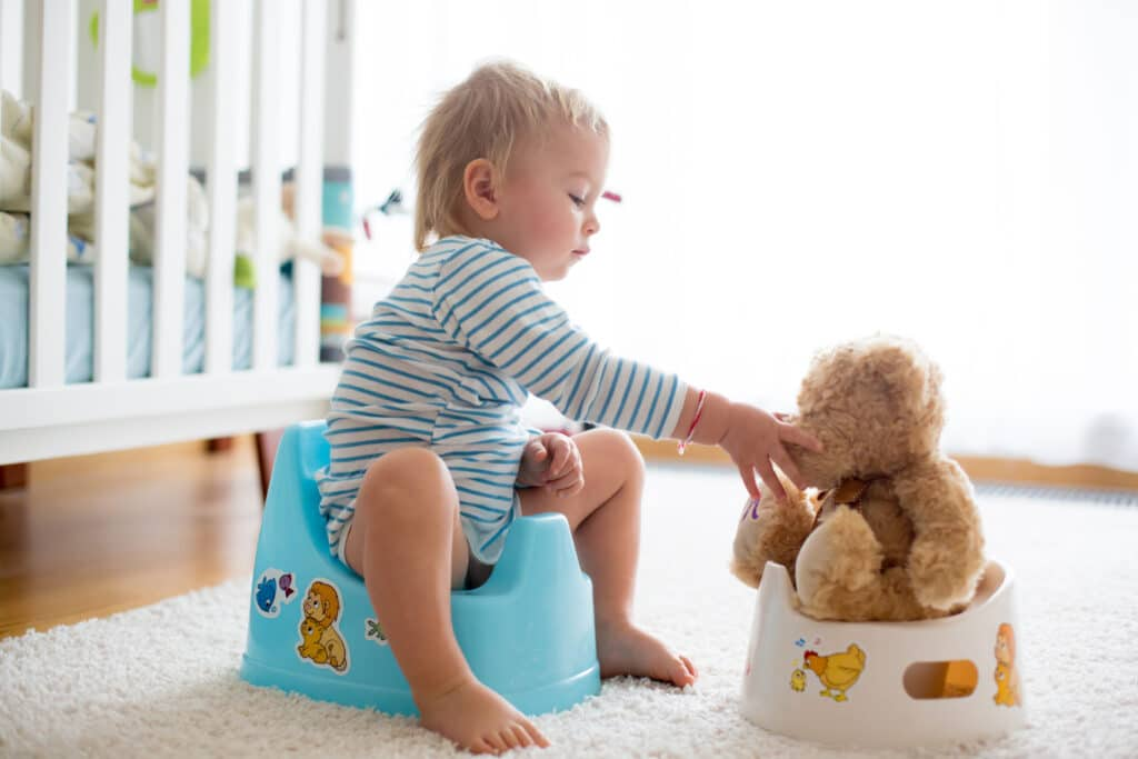 Cute toddler boy potty training with his teddy bear on potty