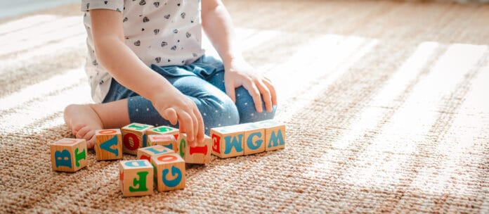 3 year old child plays with wooden cubes with colorful letters on the floor in the room a little girl is building a tower at home or in the kindergarten. Educational toys for young children.