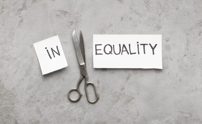 Word Inequality cut with scissors to two parts In and Equality, gray background, top view