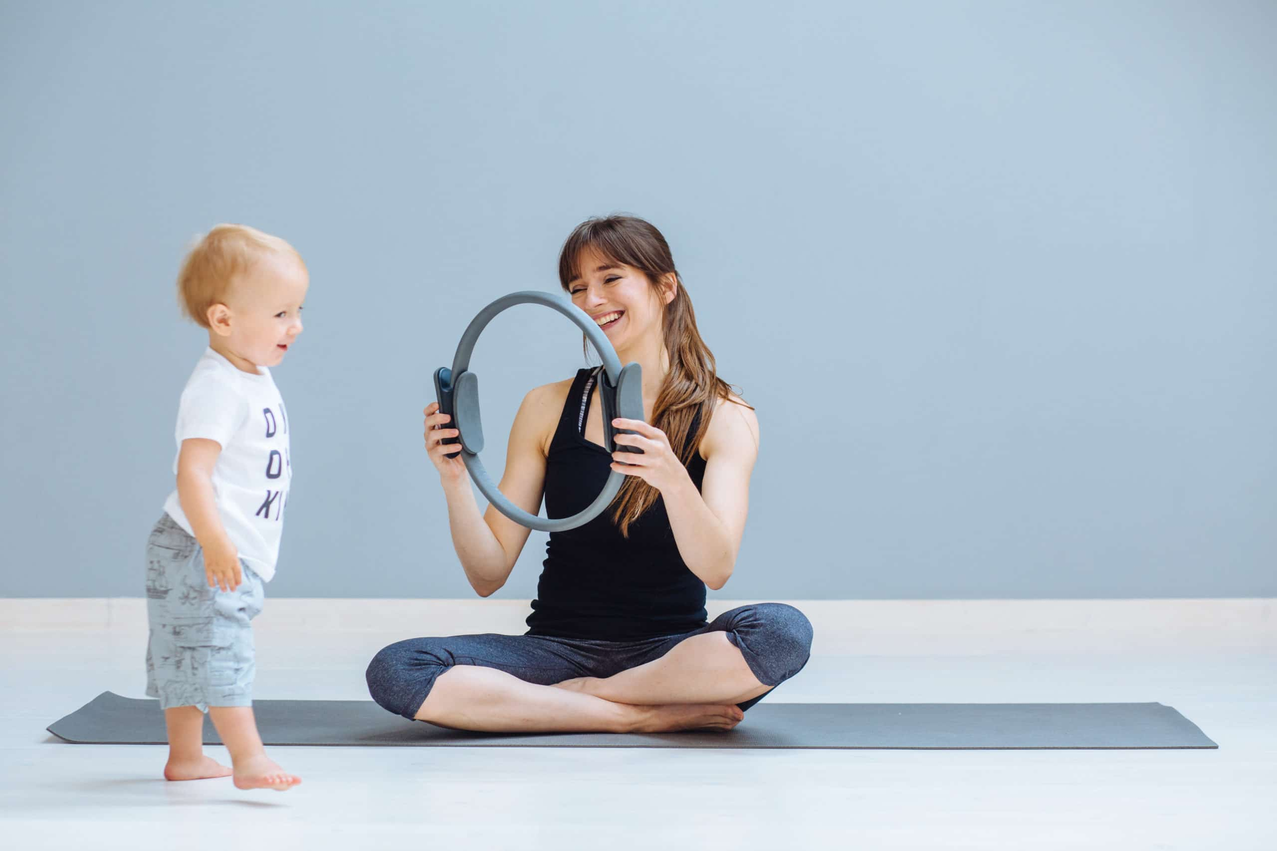 Woman exercising with a pilates ring and her baby