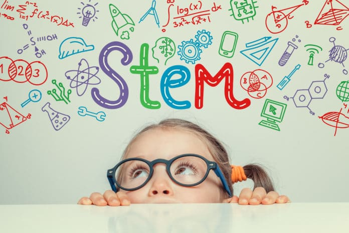 A little girl looking up at a cartoon drawing of the word STEM