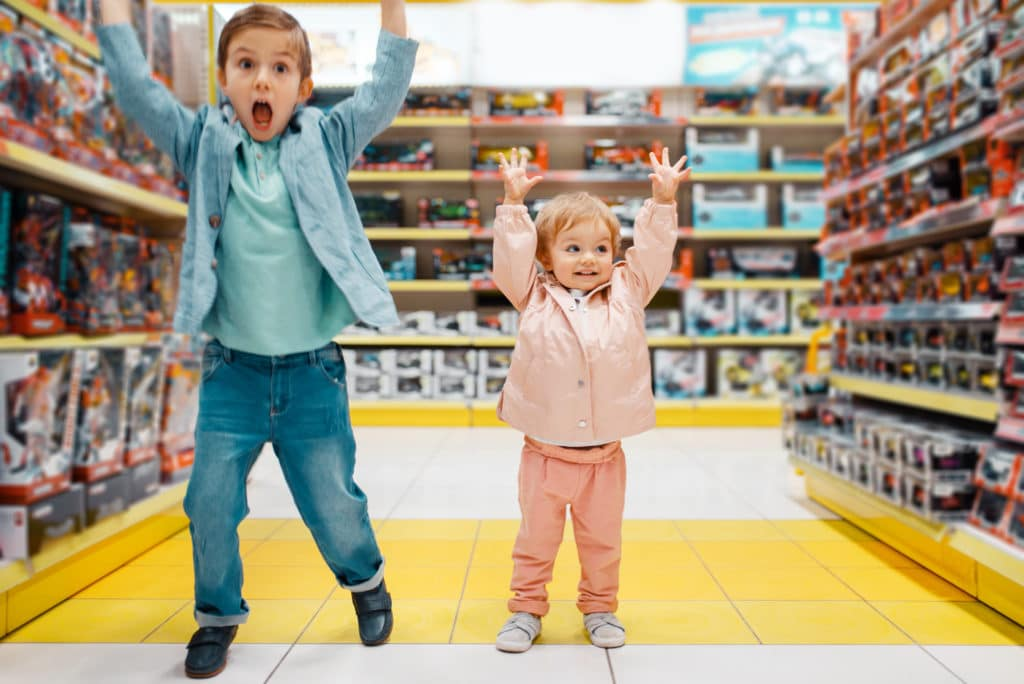 Little boy and girl raised their hands up at the shelf in kids store, happy children. Brother and sister choosing toys in supermarket, family shopping, young customers