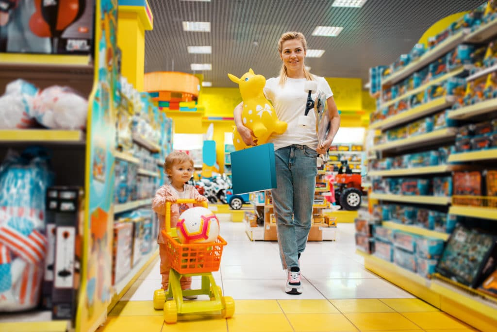 Mother with her little girl buying a lot of toys in a local toy store