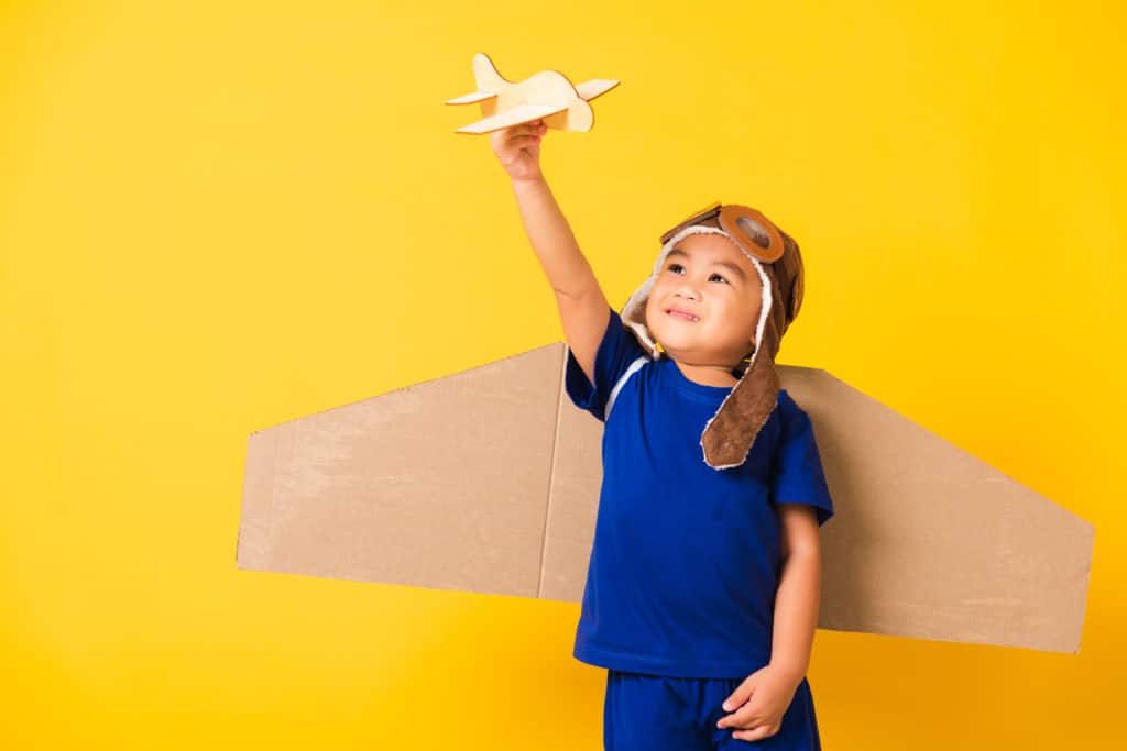 Happy boy playing with a toy airplane and wearing carboard wings