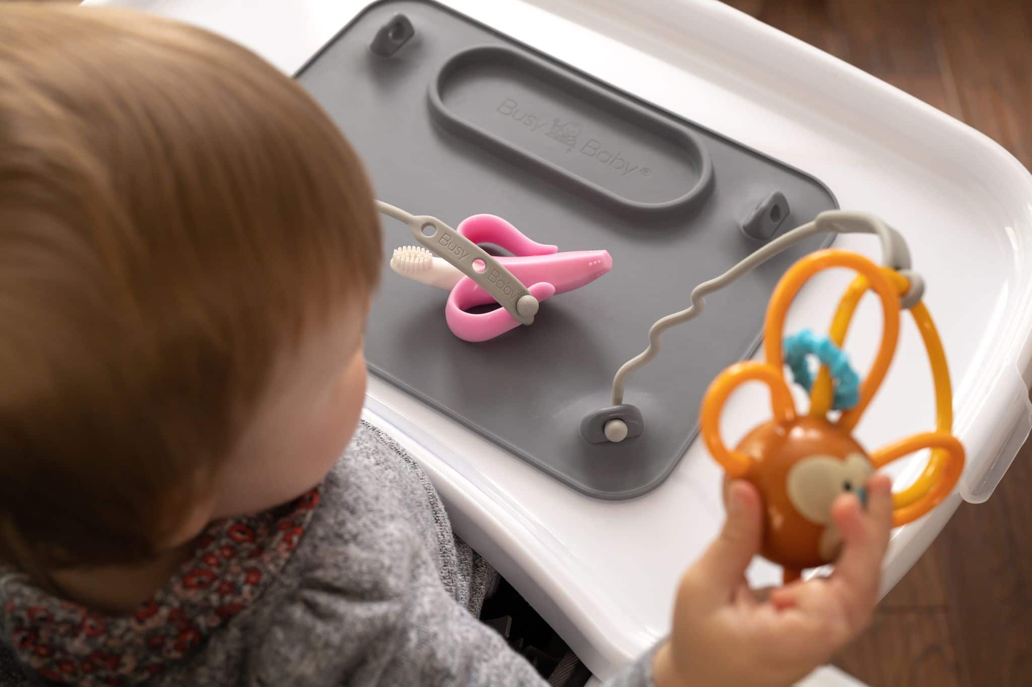 A baby playing with a Busy Baby Mat at a highchair