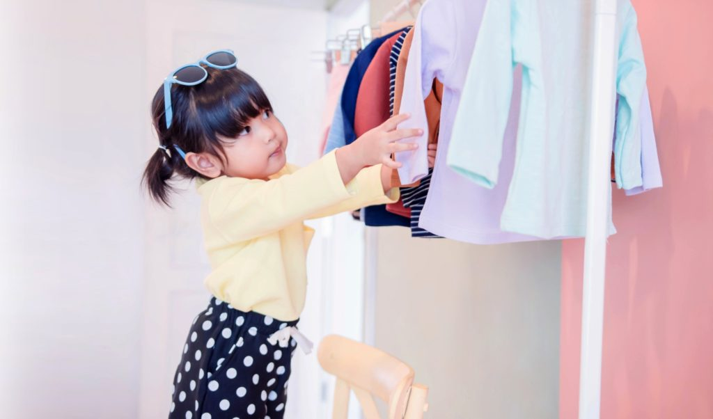 A toddler girl choosing her won clothes from a rack.