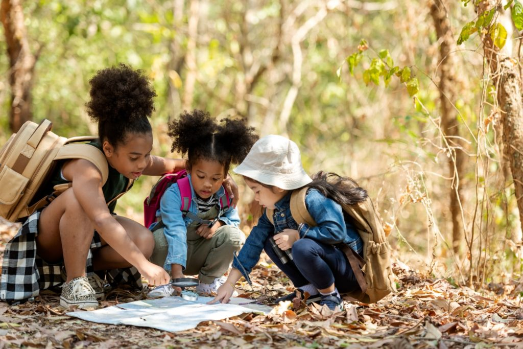 Three kids exploring nature while backyard camping looking and pointing at a map.